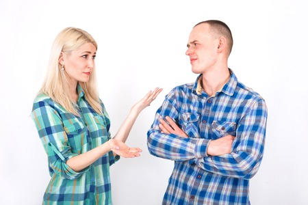 Young man and woman are arguing in the studio on a white background.