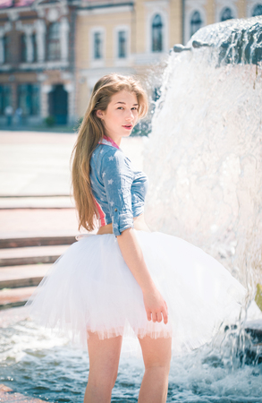 Cute young woman in fluffy skirt near the fountain