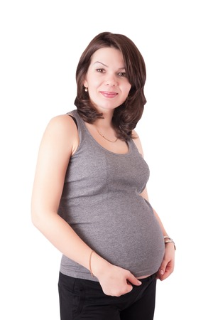 Portrait of a cute young pregnant woman in the studio. Isolated on white background.