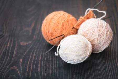 Skeins of wool thread for knitting on a wooden background. Stock Photo