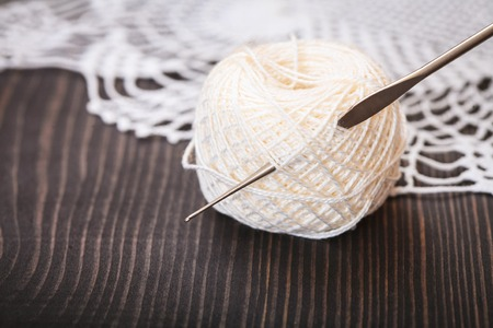 Skein of white yarn and crochet hook on a wooden table close-up