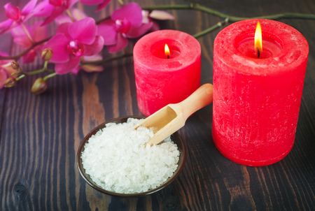 Sea bath salt, candles and flowers on a wooden background. The concept of relaxation and spa procedures.