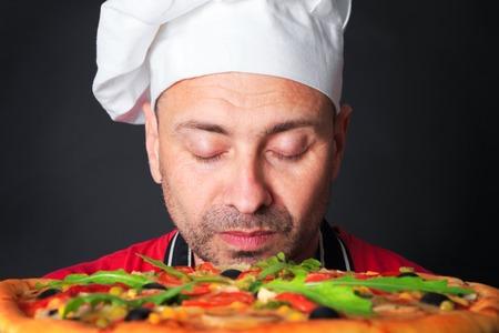 スタジオでピザと幸せの魅力的なクックの肖像画、黒の背景