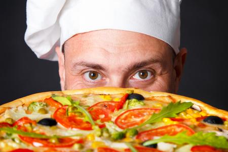 Portrait de cuisinier attrayant heureux avec une pizza en studio un fond noir