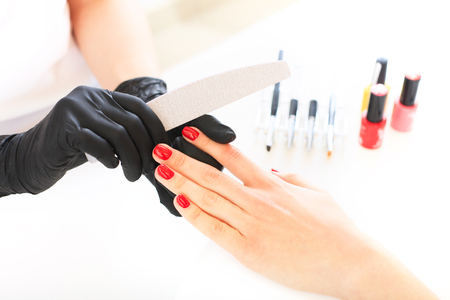 Beauty salon, hand care. Studio photography. The process of caring for the hands. Nails filing with file.