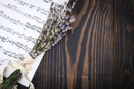 Lavender and paper music notes on old wooden background in vintage style, top view. Stock Photo