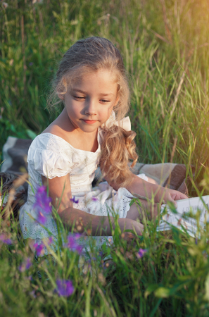 Cute little girl reading book on nature