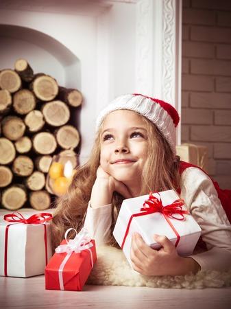 Lovely girl in santa hat lying on floor in red dress, studio shot, toning in vintage style.