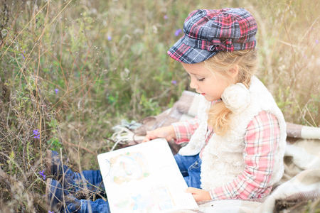 Little cute little girl is reading a book in nature against a background of autumn meadow.