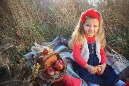 vestidos de epoca: Niña en la naturaleza con una canasta de frutas y libros.