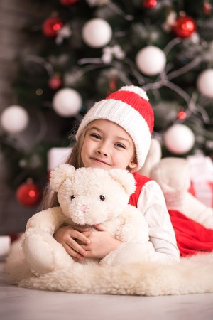 Lovely girl in santa hat sitting on the floor near the Christmas tree with a bear, studio shot, toning in vintage style. Stock Photo