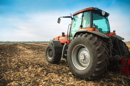 plowing: Modern red tractor in the field on a bright sunny day Stock Photo