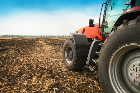 Modern red tractor in the field close-up on a bright sunny day Stock Photo