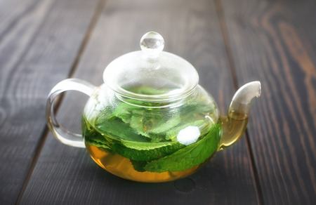Teapot with mint tea close-up on the table. Herbal infusions and healthy food.