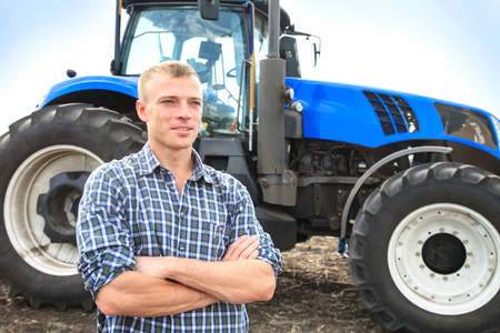 Young attractive man near a tractor. Concept of agriculture and field works.