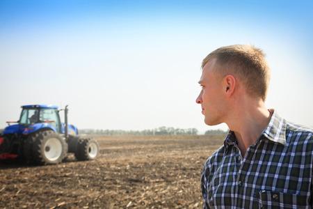 背景にトラクターとフィールドの若い男。農業とフィールドの仕事のコンセプトです。