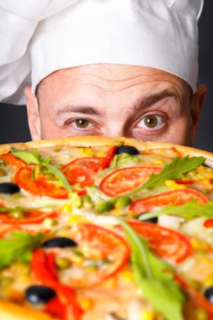 スタジオで黒い背景でピザと幸せな魅力的な料理人の肖像画