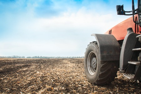 Modern red tractor in the field close-up on a bright sunny day Reklamní fotografie