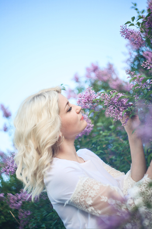 Beautiful woman in a spring garden with blooming lilacs.