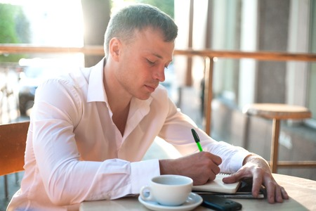 Man writing on notebook or planner with smartphone and coffee on the table at outdoor cafe.