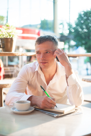 Young man drinking coffee in cafe and using phone. Business people outdoors portrait.