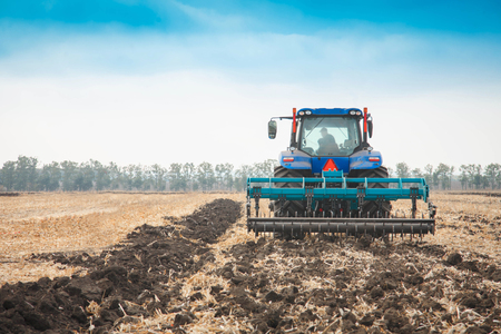 Modern tractor in a field on a sunny day. The concept of work in a fields and agriculture industry.