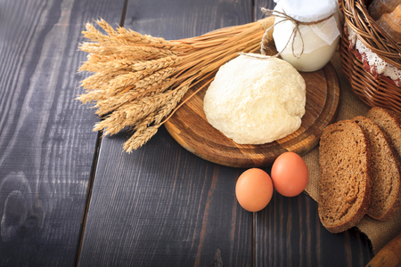 Farm products: eggs, milk, fresh bread on a wooden table Stock Photo
