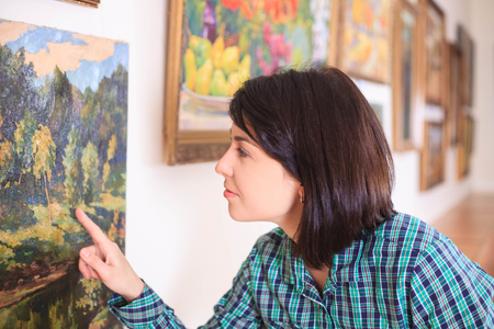 Young woman looking at painting in art gallery.