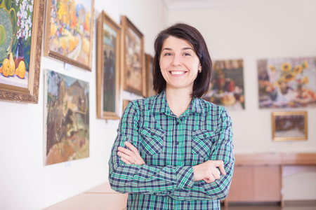 A young pretty smiling woman in a picture gallery. Reklamní fotografie