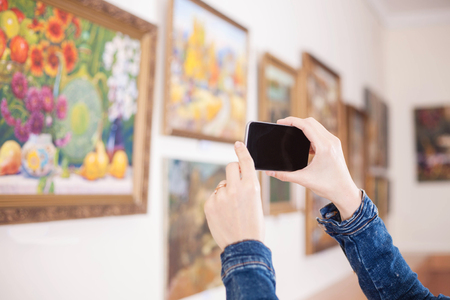 Woman photograph a painting at an exhibition of the art gallery. Stock Photo