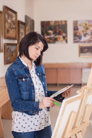 Cute young woman painting a picture near an easel in a creative studio.