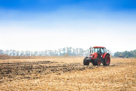 Modern red tractor working on the field on a autumn day