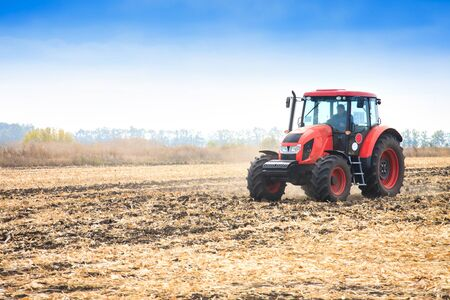 Modern red tractor working on the field in autumn day Banco de Imagens - 150552600