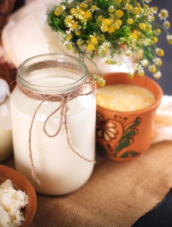 A can of milk and other dairy products on the table. Still life in rural style. Farmers cow dairy products. Stock Photo