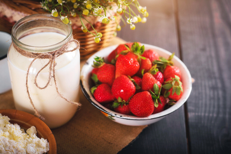 Still life of farm products. Milk and strawberry on the table close-up.