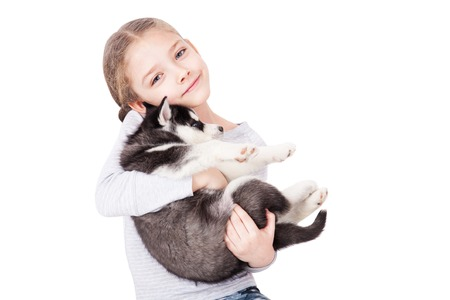 Cute little girl hugging a husky puppy, isolated on a white background.