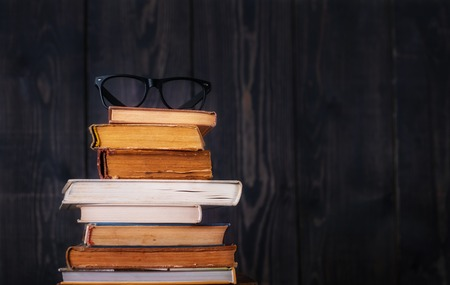 Stack of hardback books with reading glasses on dark wooden background. Back to school. Copy space. 写真素材