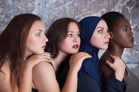 Retrato de cuatro niñas con diferente color de piel y nacionalidad en el estudio.