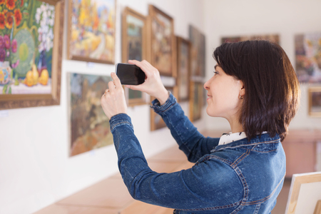 Woman photograph a painting at an exhibition of the art gallery. Reklamní fotografie