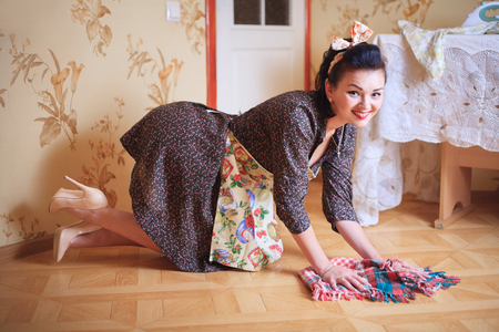 Young beautiful woman washes the floor. Shooting in pinup style, retro.