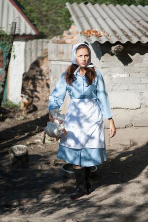A woman in a village dressed in country style is holding a goose. Shooting in retro style.