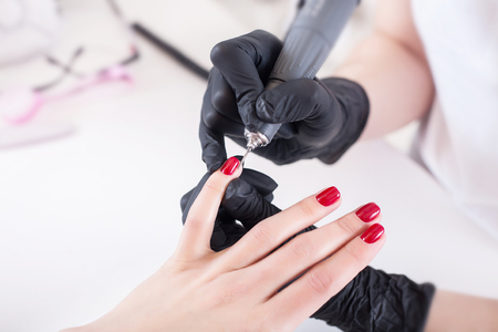 Manicurist, nail artist handles nails with manicure milling cutter. Beauty service, nail salon, health care and cosmetics. Close up. Stock Photo