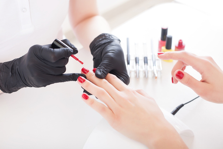 A manicurist in gloves paints a female nails with red lacquer. Beauty service, salon, health care and cosmetics. Close up.