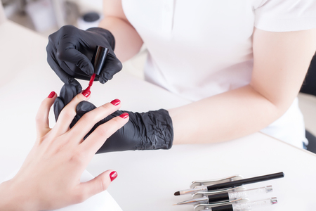 A manicurist in gloves paints a clients nails with red lacquer. Beauty service, salon, health care and cosmetics. Close up.