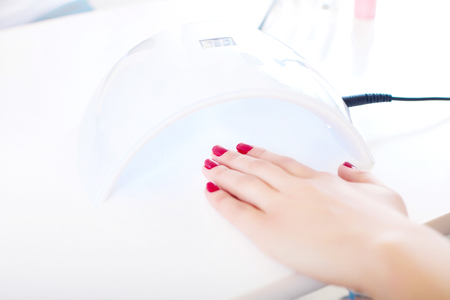 Closeup of a female hand inside a UV or LED lamp, curing her recently applied gel nail polish at a salon. Stock Photo