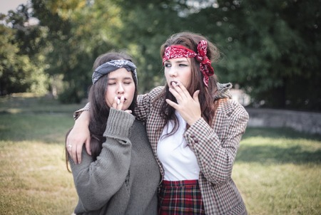 Two informally dressed girls walking down the street with cigarettes. Teenage problems.