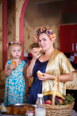 Mom and daughter, portrait in retro style in the vintage interior of the home kitchen. Banco de Imagens