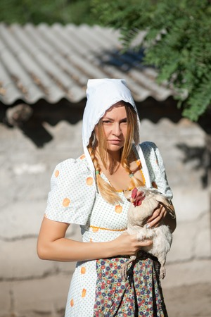 A woman in a village dressed in country style is holding a hen. Shooting in retro style.
