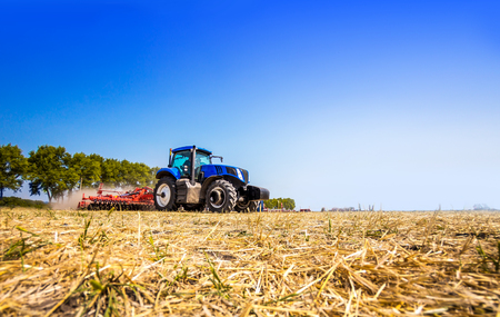 The tractor plows the field, cultivates the soil for sowing grain. The concept of agriculture and agricultural machinery. Reklamní fotografie