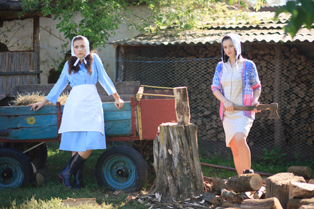 Two young women in the village. Woman holds an ax in her hands. Portrait in retro rural style. Imagens